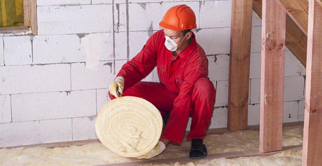 Homme déroulant un rouleau d'isolant thermique